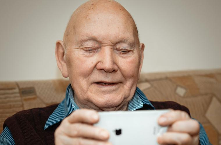Elderly man sitting on a sofa holding at an i-phone